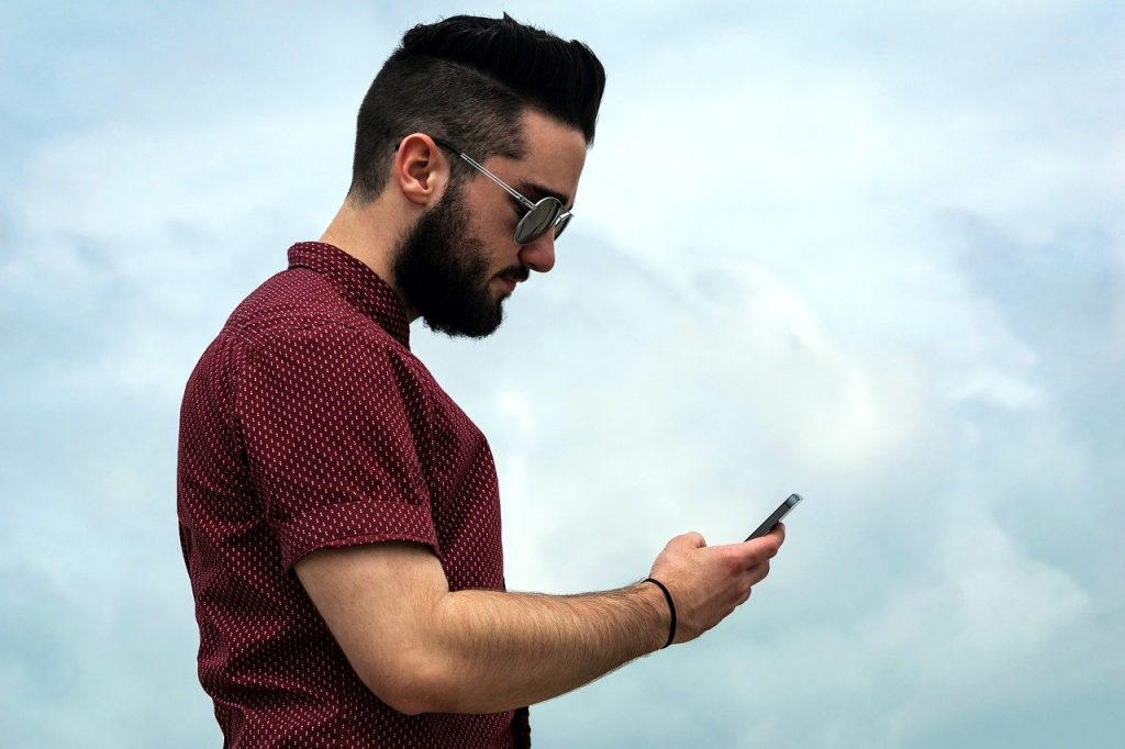 barbe hipster homme de profil avec telephone en main